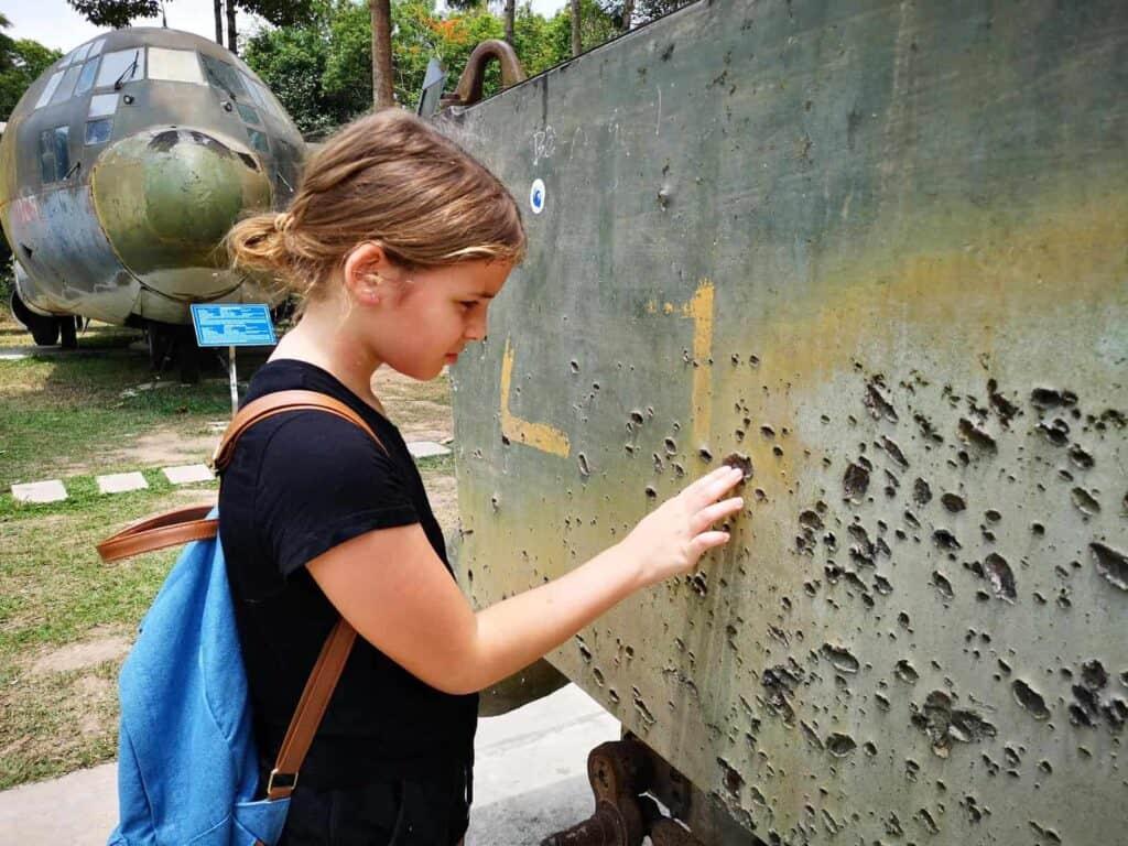 Milla Examining Bullet Holes on a Tank