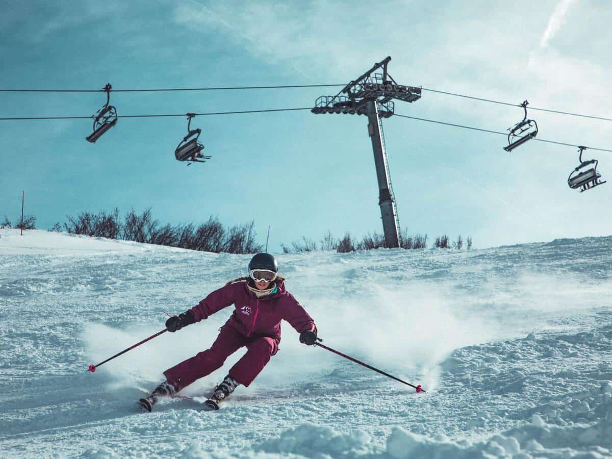 Person snow skiing in front of chairlift