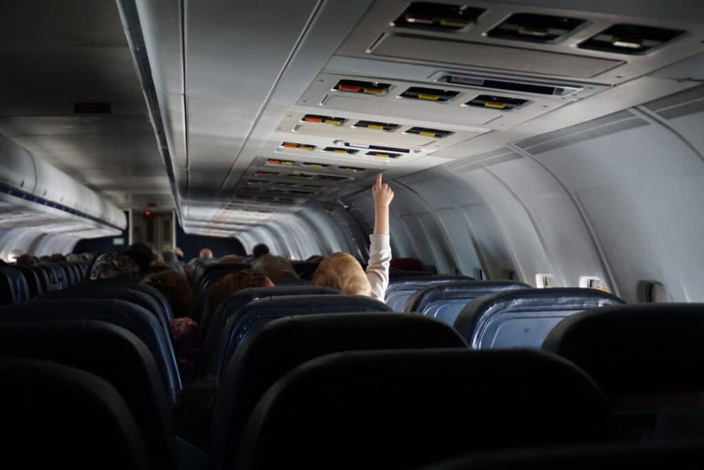 Flying with children, baby on plane reaching to ceiling